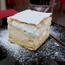 10.Napoleonka - Varsovia (Factor dulce: 1/10 - 0.06 cafés/1000hab) La Napoleonka, también llamada Kremówka, es una tarta de nata polaca hecha con dos capas de hojaldre, rellena de crema batida y decorada con azúcar en polvo o glaseado en la parte superior. Una anécdota sobre el Papa Juan Pablo II dice que, una vez, ha comido 18 porciones de Napoleonka de una sentada por una apuesta con un amigo. Dónde probarla: En Lukullus, aunque tiene muchas tiendas por toda la ciudad, tres de ellas están justo en el centro, así que ¿por qué no probarlas todos? En Lukullus puedes comerte un trozo de Napoleonka tradicional además de otros muchos dulces. Precio: 7,90€ Calorías: 429 kcal / 100g Cómo quemarla: 123 minutos de caminata: explorando la ciudad o... para ser más efectivo, sube las escaleras de los 42 pisos del Palacio de la Cultura y las Ciencias, las calorías de la Napoleonka desaparecerán de tu sistema después de este ejercicio.