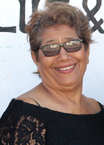Esther Gonzalez, Light and Salt Ministries Sewing Instructor, stands in front of some greenery in a blue shirt and black a wall in a black dress, smiling.