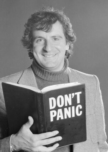 """Douglas Adams sosteniendo unn libro con una de las frases más míticas de """"Guía del Autoestopista Galáctico"""""""