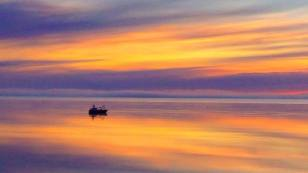 """""""A lone vessel in the cook inlet off the shore of Nikiski appears to be floating in the sky as the sun set paints a perfect ending to the day."""" J.N. Photo by Jeff Nelson"""