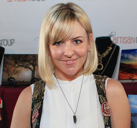 Actress Helene Yorke posing with the Vitrine Designs bullet necklace at GBK Golden Globes gift lounge.