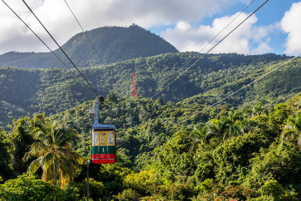 Colorful cable car over lush green tropical landscape in Puerto Plata, DR