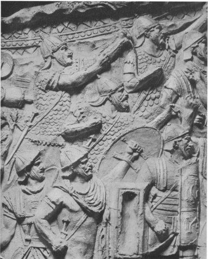 Rilievo dalla Colonna Traiana: soldati ausiliari e romani combattono assieme. I barbari ausiliari indossano corazza a scaglie e un elmo di tipo spangenhelm diverso da quello dei soldati romani