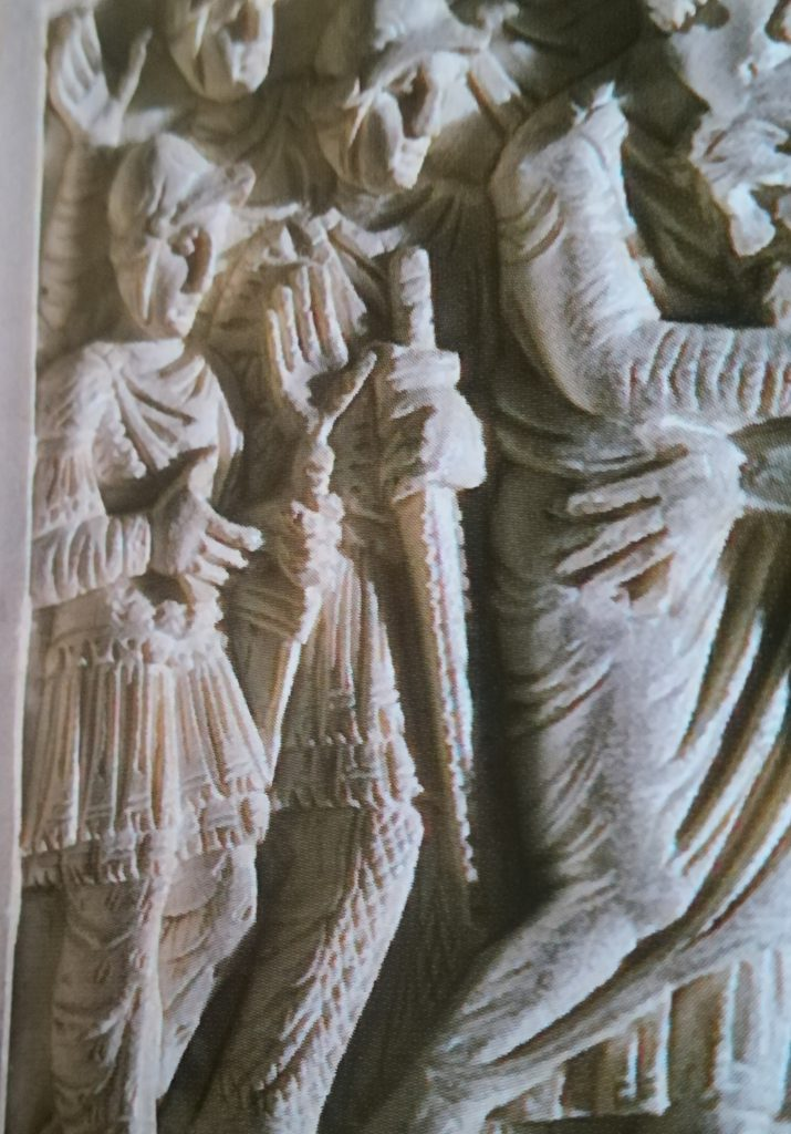 """Sul lato sinistro della cattedra eburnea appare la formella in cui secondo il racconto della Genesi Giuseppe riabbraccia il padre. Il dettaglio in foto mostra due soldati con pantaloni decorati in modi differenti. Uno dei due è simile a quello raffigurato nelle figure di """"barbari"""" dellavorio Barberini."""