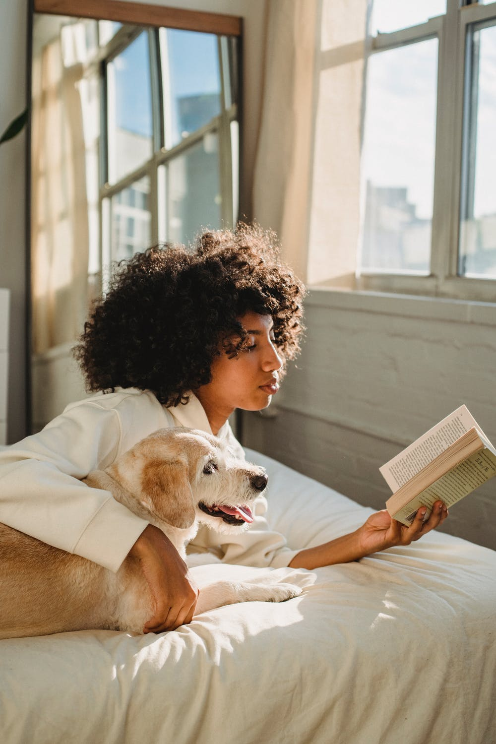 black woman reading a book with dog on bed on an apartment