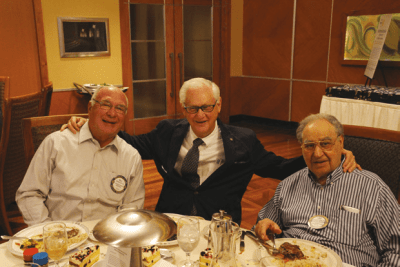 Three distinguished gentlemen, Messrs. Stieren, Rulffes and Fathie, enjoy lunch together.