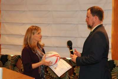 President Michael awards speaker Kelly Burton with our Share What you Can award. She presented Michael with a rugby ball signed by members of the USA Sevens Rugby team.