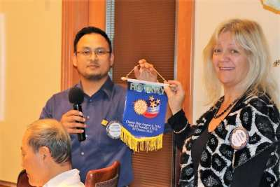 Sergeant at Arms Rose Falocco accepts a banner from Aaron Campillo from a Philippine Rotary Club.