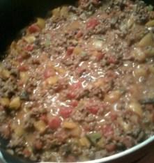 ground beef simmering in variety of cut vegetables