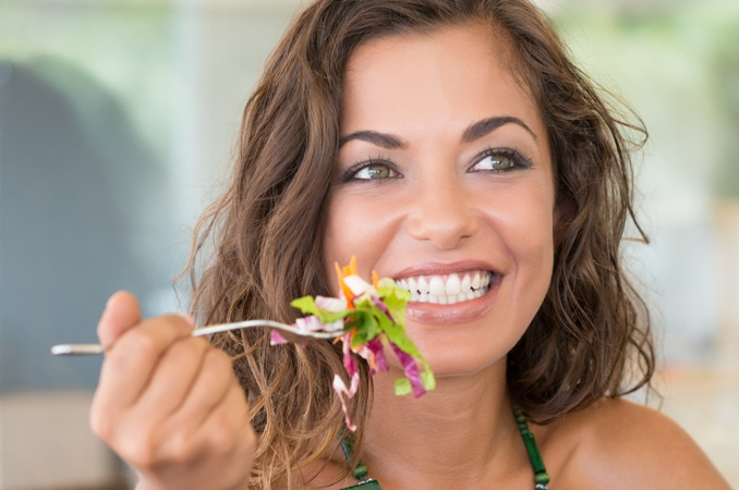 Smiling Woman eating healthy plan for long-term change