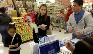 Grocery shoppers stop at a Blue Cross Blue Shield kiosk promoting the Affordable Care Act enrollment