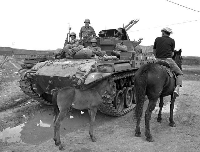 """In the immediate aftermath of the June 5, 1967 Tierra Amarilla courthouse raid, New Mexico National Guard tanks and troops scoured northern New Mexico in search of Reies Lopez Tijerina and other Alianza members. In this photo, troops chat with a Canjilon resident."" (Ray Cary/Journal File)"
