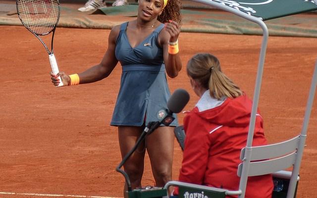 Serena Williams on tennis court at Roland Garros talking with umpire