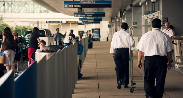 airport drop off area; people hurriedly walking along the curb area