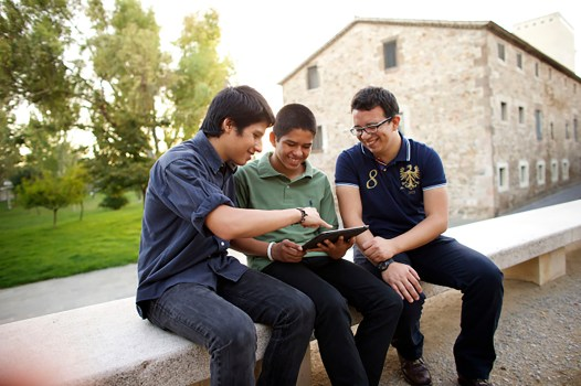 three young men on a tablet, smiling and looking at things