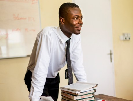 A teacher stands at the front of his classroom with hymnbooks and scriptures on a table in front of him.