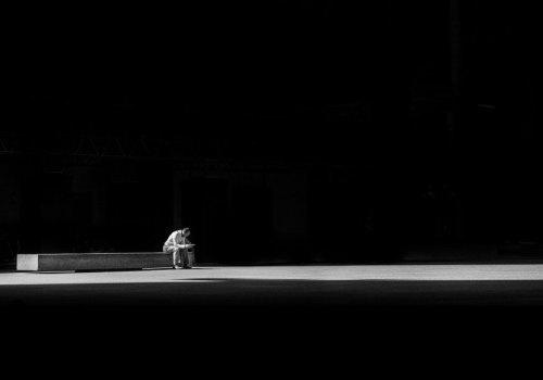 Man sitting alone on bench in darkness
