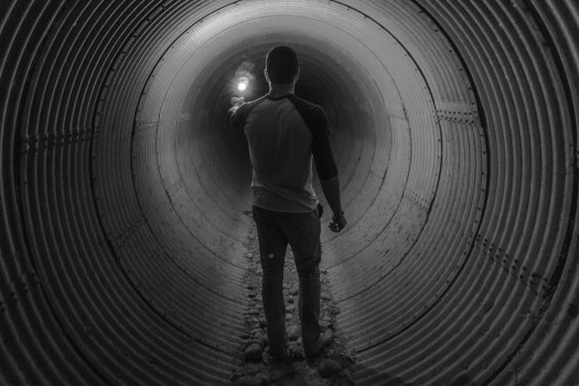 Man with a light in a dark tunnel.