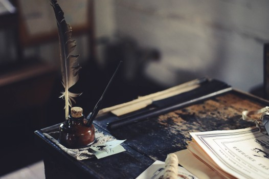 desk with quill and paper