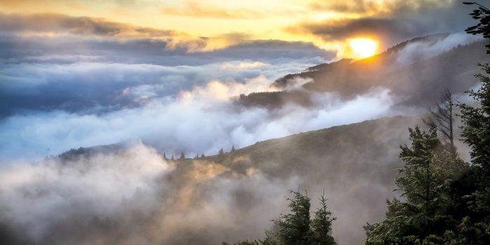 Sun rising over cloudy mountains