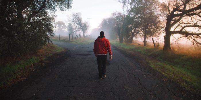 Man in red sweatshirt walks along a road