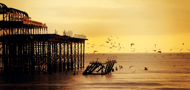 Old pier at sunset with flying seagulls.