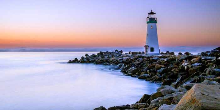 A lighthouse on the edge of a rocky shore.