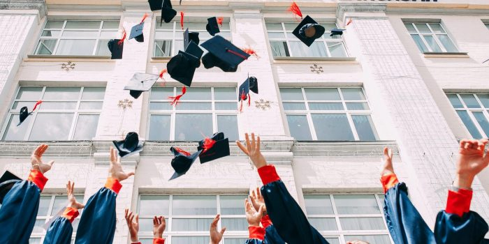 College graduates throwing their blue caps with red tassels into the air next to a tall building with windows.