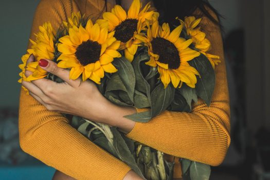 woman holding bunch of sunflowers