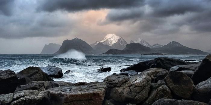 Waves Crashing on Rock Near Mountains during Daytime