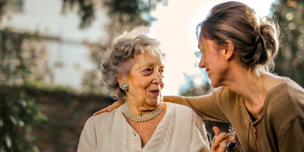 A woman laughing with her grandmother in a garden