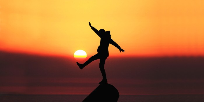 silhouette of a person balancing on a boulder on the beach, sun setting in the background.