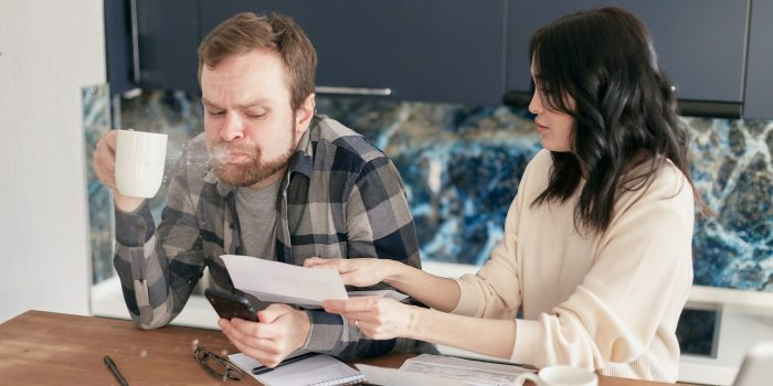 Couple sitting at table doing finances, one is visibly shocked