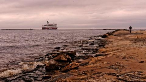 Bild: Eine Fähre nach Tallin fährt zwischen den beiden Leuchttürmen von Daugavgrīva (links)  und Mangaļsala (rechts) aus dem Hafen in den Golf von Rīga aus. OLYMPUS OM-D E-M5 mit M.ZUIKO DIGITAL ED 12‑40mm 1:2.8. ISO 640 ¦ f/7,1 ¦ 18 mm ¦ 1/1000 s ¦ kein Blitz. Klicken Sie auf das Bild um es zu vergrößern.
