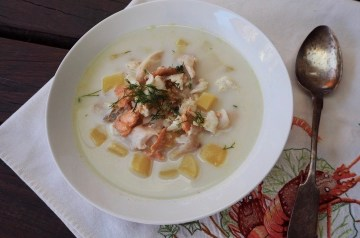 fish soup in a white plate with silver spoon and white napkin