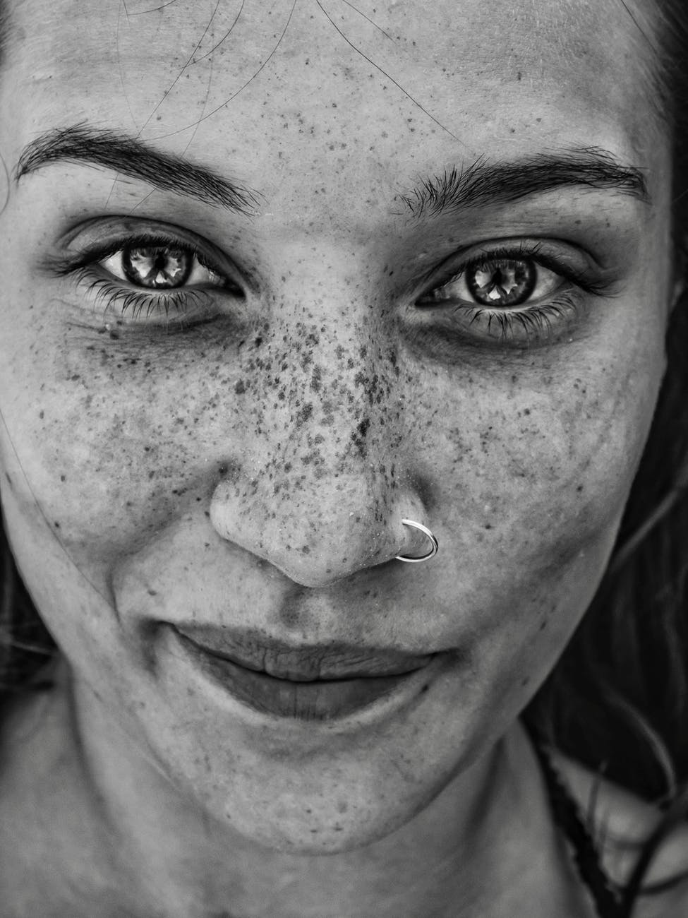 cheerful woman with freckles looking at camera