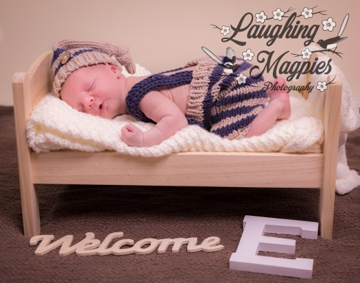"""A pink and cuddly newborn boy rests cozily on a perfectly sized bed along with the text, """"Welcome E"""" and marked with Laughing Magpies Photography's watermark."""