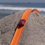 POV Footage of Cars Racing to the Finish on a Large Hot Wheels Track That Was Built on a Beach