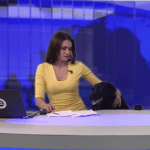 Russian Newscaster Surprised by a Big Black Dog Who Crawled Out From Under Her Desk While On-Air