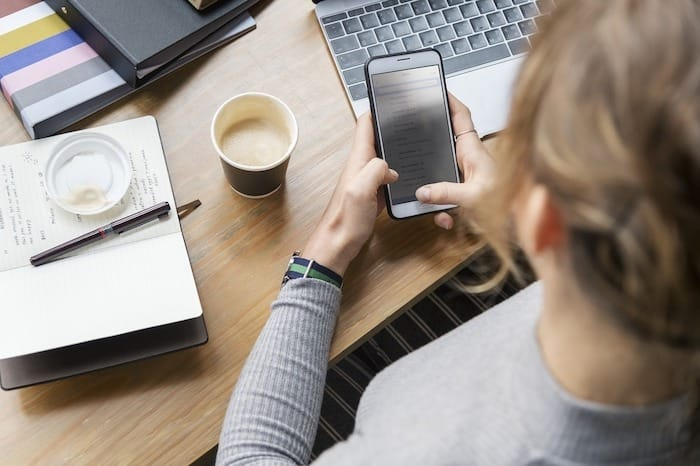Woman wonders what is Slack while looking at phone and computer