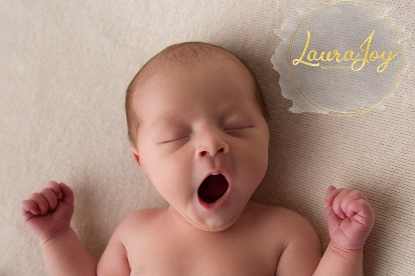 Picture of Newborn baby yawning on natural background.. Image by Laura Joy Photography - Newborn Photographer based in Glasgow.