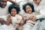 cheerful multiracial family having fun in bed during weekend