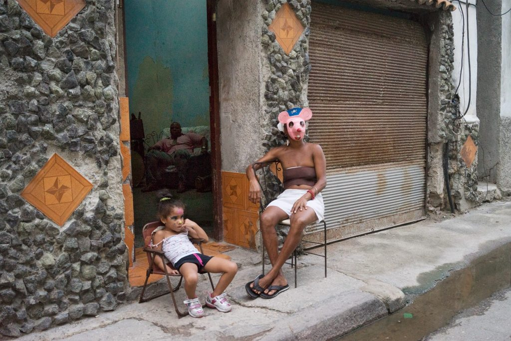 Image by Alexa Hoyer: woman in face mask with daughter sit in street