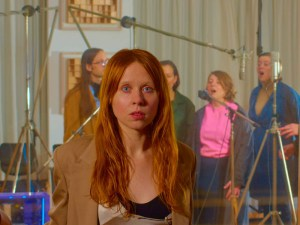 Flame haired Holly Herndon looks into camera with backing singers behind