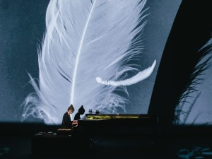 Poppy Ackroyd plays grand piano with giant feather visual background