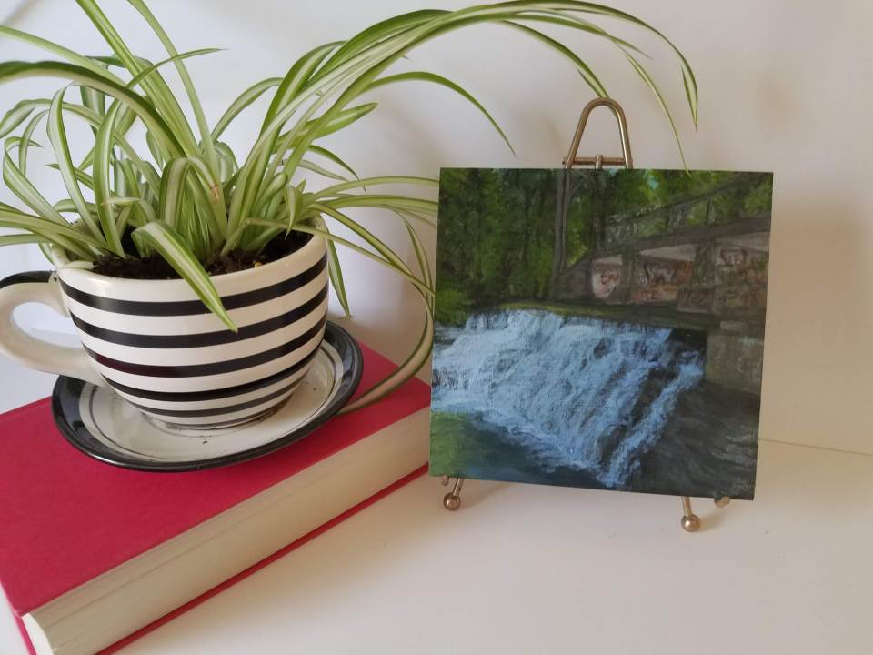 Photo with book and plant of Papermill Falls by Laura Jaen Smith. Acrylic landscape painting of waterfall in Avon from 50 NY Waterfalls Project.