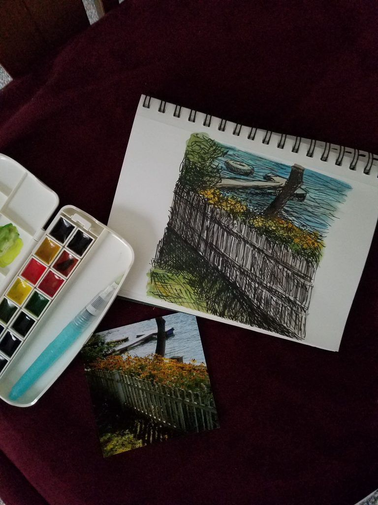Photo of watercolor and ink lakeside cottage view painting with watercolor palette, brush, and reference photo