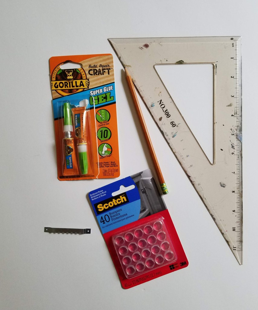 Art Tip: Low Cost Art Hanging. Materials shown painting, gorilla glue, triangle ruler, pencil, bumpers, and sawtooth hook.