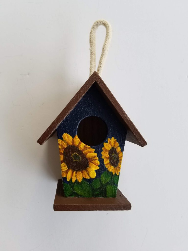 Navy Sunflower Birdhouse by Laura Jaen Smith. Squared small birdhouse with brown roof and base, hand-painted sunflowers with navy background.