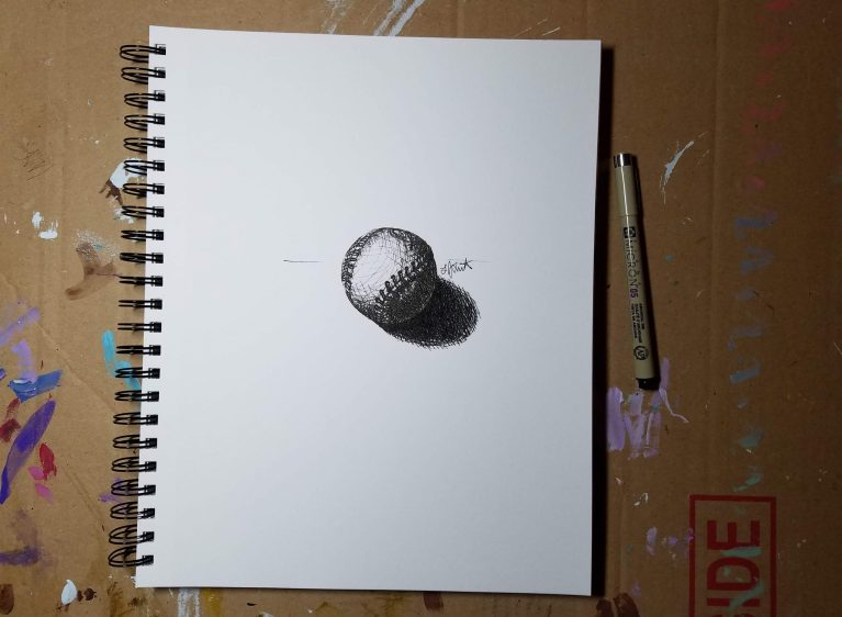 Sketchbook view with pen of Baseball by Laura Jaen Smith. Black and white ink drawing of a baseball.